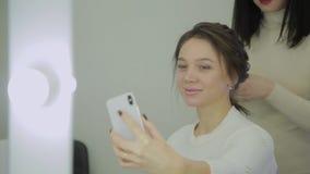 La mujer muy hermosa y moderna hace un selfie cuando ella hace su pelo en un salón de belleza metrajes