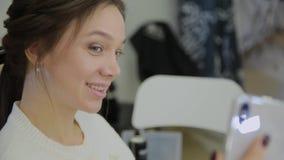 La mujer muy hermosa y moderna hace un selfie cuando ella hace su pelo en un salón de belleza almacen de video
