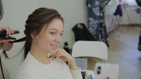 La mujer muy hermosa y moderna hace un selfie cuando ella hace su pelo en un salón de belleza almacen de metraje de vídeo