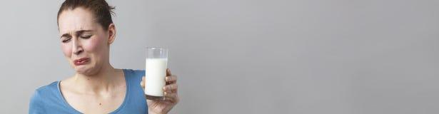 La mujer nauseabunda asqueada en tener que adietar con la leche blanca Fotos de archivo libres de regalías