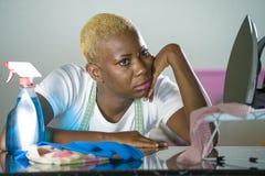 La mujer negra afroamericana triste y deprimida hermosa joven con la botella viva detergente y la cerrajería trastornó en casa el foto de archivo