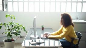 La mujer negra atractiva trabaja en el ordenador en oficina almacen de metraje de vídeo