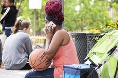 La mujer negra con las trenzas rojas se sienta en el lugar de acopio que lleva a cabo un baloncesto y que habla en un teléfono ro Foto de archivo