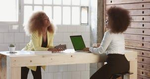 La mujer negra dos con el pelo afro en oficina tiene una pequeña charla durante un proceso del trabajo metrajes