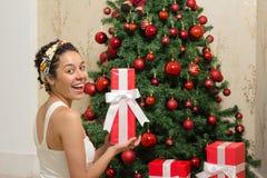 La mujer negra es feliz con su regalo de Navidad Árbol adornado y fotografía de archivo libre de regalías