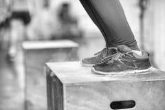 La mujer negra está realizando saltos de la caja en el gimnasio Foto de archivo