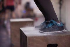 La mujer negra está realizando saltos de la caja en el gimnasio Imagenes de archivo