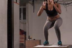 La mujer negra está realizando saltos de la caja en el gimnasio Imagen de archivo