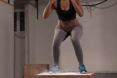 La mujer negra está realizando saltos de la caja en el gimnasio Fotografía de archivo libre de regalías