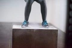 La mujer negra está realizando saltos de la caja en el gimnasio Imagen de archivo libre de regalías