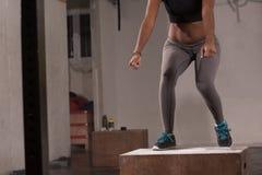 La mujer negra está realizando saltos de la caja en el gimnasio Fotografía de archivo