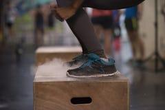 La mujer negra está realizando saltos de la caja en el gimnasio Fotos de archivo