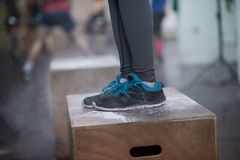 La mujer negra está realizando saltos de la caja en el gimnasio Fotos de archivo libres de regalías