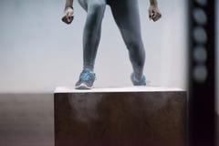 La mujer negra está realizando saltos de la caja en el gimnasio Foto de archivo libre de regalías