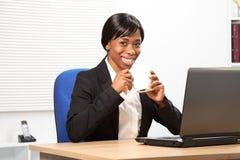 La mujer negra hermosa bebe el café en el trabajo Imagen de archivo libre de regalías