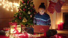La mujer negra joven está charlando en línea usando el ordenador portátil y se está sentando cerca del árbol de navidad adornado almacen de video