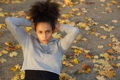 La mujer negra joven hermosa que el hacer se sienta sube Imagenes de archivo