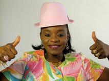 La mujer negra que desgasta un sombrero del color de rosa manosea con los dedos para arriba Foto de archivo libre de regalías