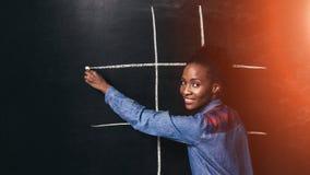 La mujer negra se divierte que juega el dedo del pie del tac del tic en la pared Foto de archivo libre de regalías