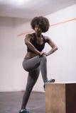 La mujer negra se está preparando para los saltos de la caja en el gimnasio Imagenes de archivo