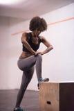 La mujer negra se está preparando para los saltos de la caja en el gimnasio Foto de archivo