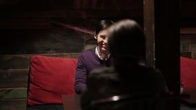 La mujer negra y el hombre blanco hacen diálogo en el restaurante Diversos amigos de la raza almacen de video