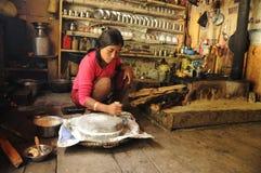 La mujer nepalesa muele el arroz, Nepal Imagen de archivo libre de regalías