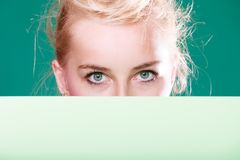 La mujer observa detrás de la muestra blanca Fotografía de archivo libre de regalías