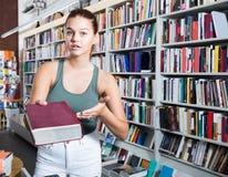 La mujer ofrece un libro en una librería Fotos de archivo libres de regalías