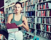 La mujer ofrece un libro en una librería Imagenes de archivo