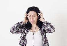 La mujer oyó una música muy mala o un ruido desagradable en los auriculares, ella torció la cara y quiere quitar los auriculares Fotografía de archivo libre de regalías