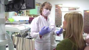 La mujer paciente del dentista del doctor de las mentiras explica al paciente del diálogo almacen de metraje de vídeo