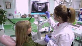 La mujer paciente del dentista del doctor de las mentiras explica al paciente del diálogo metrajes