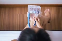 La mujer paciente que usa el incentivo-espirómetro o tres bolas para estimula el pulmón imagenes de archivo