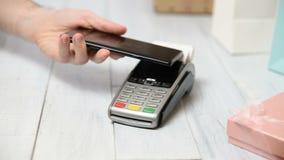 La mujer paga con tecnolog?a de NFC en un smartphone y paquete de la recepci?n del hombre de entrega almacen de metraje de vídeo