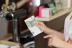La mujer paga el efectivo el desayuno en el café con los billetes de banco euro Fotografía de archivo libre de regalías