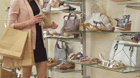 La mujer para cerca de los zapatos beige en la tienda almacen de metraje de vídeo