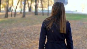 La mujer pasa a través del parque que da vuelta alrededor, mirando alrededor, las vueltas a la cámara cámara lenta de 4k 60fps Mu almacen de metraje de vídeo