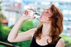 La mujer pecosa bebe el agua de la botella Fotografía de archivo