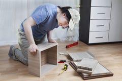 La mujer pega junta el tablero del cajón, montaje de los muebles en casa fotos de archivo