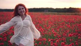 La mujer pelirroja alegre corre a través del campo de florecimiento de amapolas y da vuelta alrededor hacia cámara metrajes