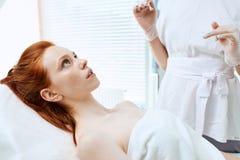 La mujer pelirroja caucásica consigue a belleza inyecciones faciales Inyección del envejecimiento de la cara fotos de archivo libres de regalías
