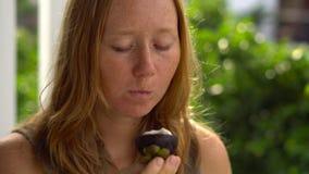 La mujer pelirroja come el mangostán jugoso fresco almacen de video