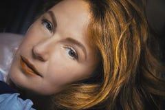 La mujer pelirroja con los labios rojos está mirando a través de la cámara Imagen de archivo