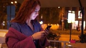 La mujer pelirroja hermosa joven utiliza del teléfono móvil en la noche en café de la calle al lado del camino con noche hermosa almacen de video