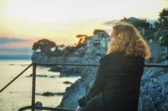 La mujer pelirroja joven hermosa, en la playa en el pueblo pesquero en Liguria, Italia disfruta de la puesta del sol imágenes de archivo libres de regalías