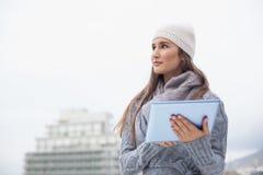 La mujer pensativa con invierno viste en usar su tableta Foto de archivo