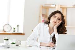La mujer pensativa con la mano debajo de la barbilla agujereada en el trabajo, mirando la sentada ausente cerca del ordenador por imágenes de archivo libres de regalías