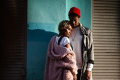 La mujer pensativa del mulato con el hairtyle de moda y su oscuridad peló al novio elegante en el sombrero rojo, soporte cerca de imagen de archivo libre de regalías