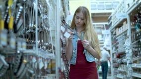 La mujer pensativa joven está mirando en las llaves en una tienda, leyendo etiquetas metrajes